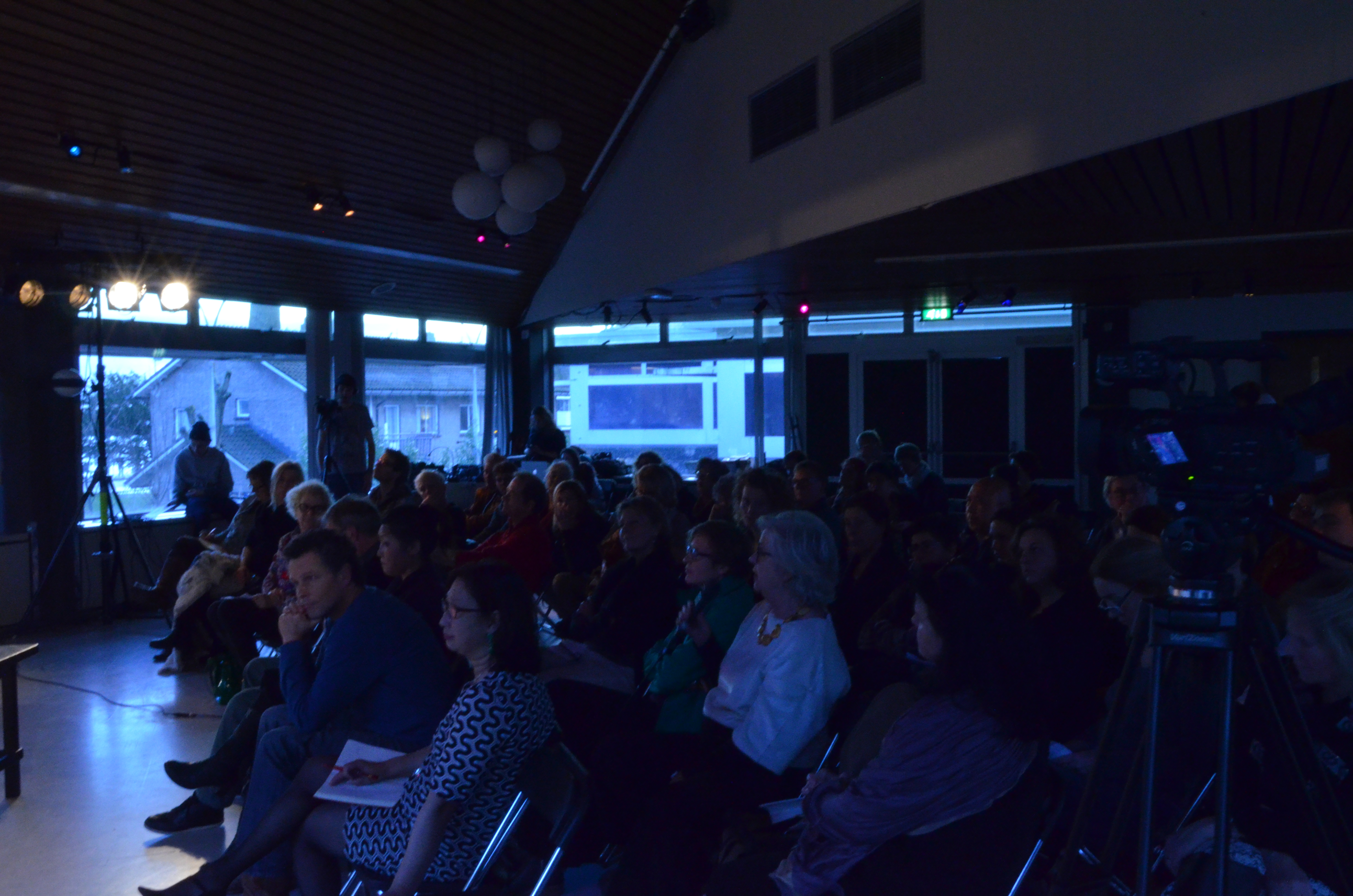 Het publiek luistert aandachtig.